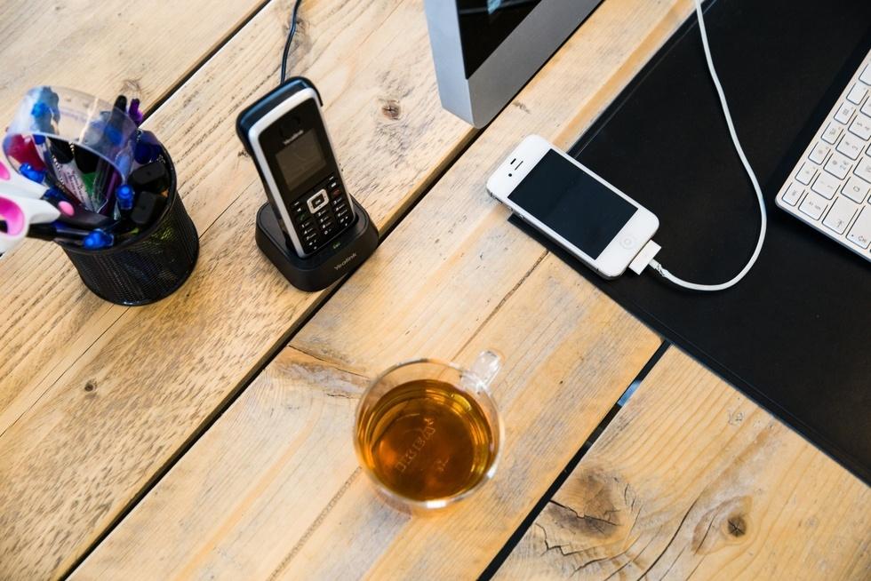 Bureau met thee en mobiel